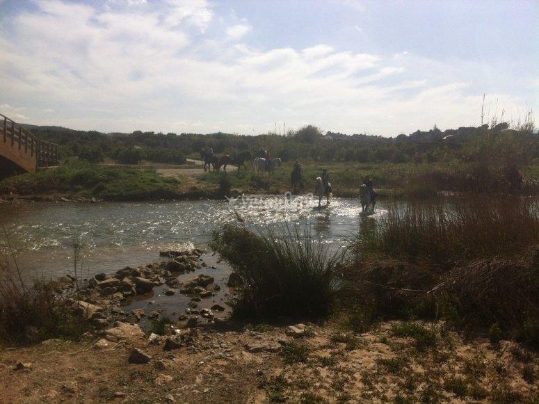 Camino a caballo a través del río