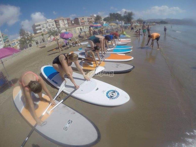在沙子练习划桨冲浪