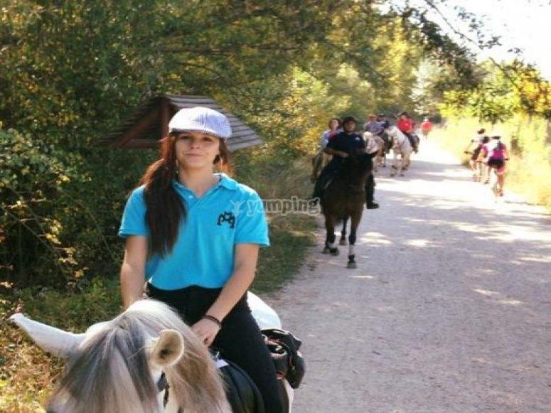 chica montada en caballo.