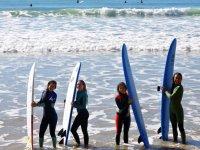 Alumnas con tablas de surf en el mar