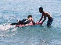 Monitor ayudando a la alumna en clase de surf
