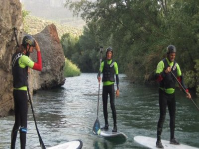 Stand up paddle surfing descending river Genil