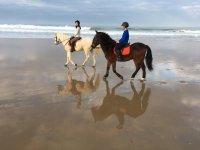 Jinete y amazona en la playa en Cadiz