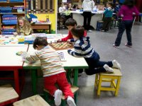 four children playing at a playroom table