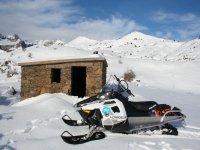 Moto en la nieve junto al refugio