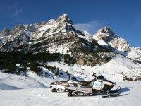 Motos de nieve en la falda de la montaña