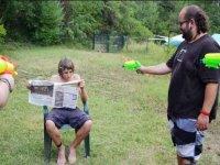monitor disparando con una pistola de agua a un nino