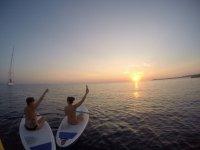 tramonto della coppia di paddle surf