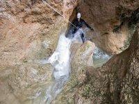 chica bajando por una cueva de agua agarrada a una cuerda