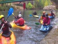 chicos con cascos en piraguas dentro del agua
