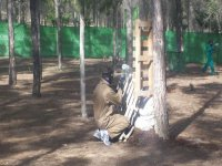 chico detras de una tabla de madera jugando al paintball