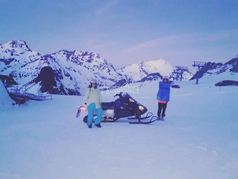 Parada junto a la moto de nieve