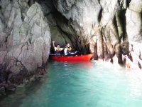 Leaving the cave in red kayak