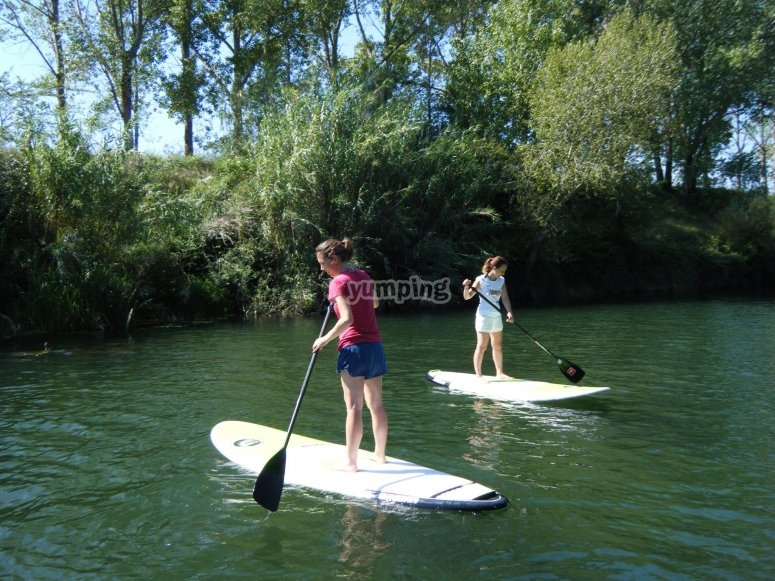 Two girls doing stand up paddle surfing Fluvià river