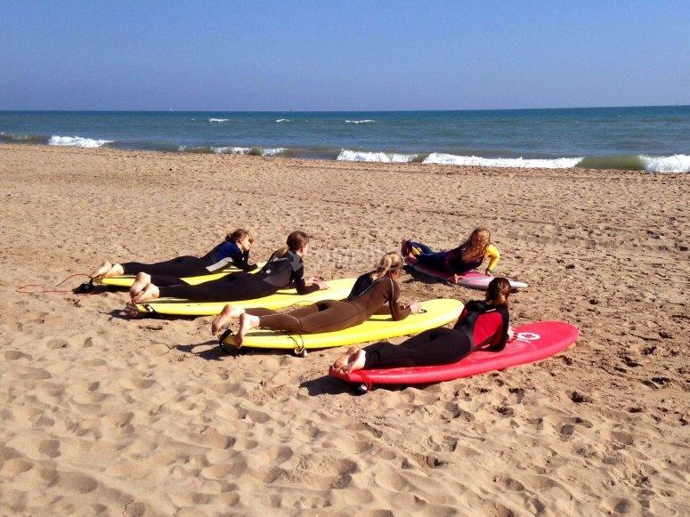 Chicas aprendiendo surf en la arena