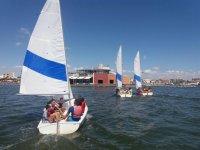 Students on three sailboats