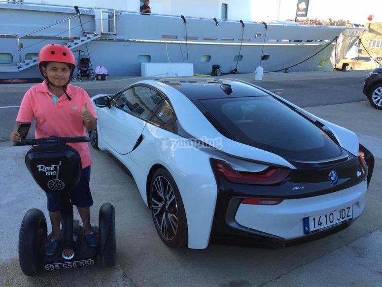Joven de segway posando junto a BMW