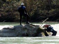 一名男子攀爬岩石河,而一个人站在岩石