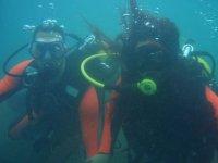 dos buceadores con neoprenos naranjas buceando en el mar
