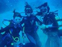 tres chicas equipadas buceando