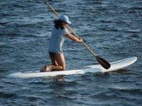 mujer de rodillas remando sobre una tabla de surf