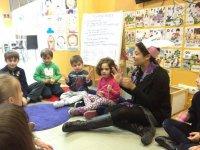 profesora y ninos en circulo cantando