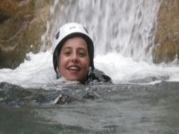 child smiling with a white helmet swimming in the water