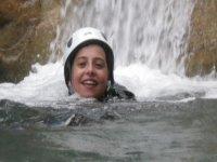 男孩微笑着戴着白色头盔在水中游泳