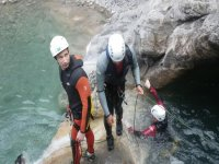 three men overcoming the obstacles of the descent of the riverbed