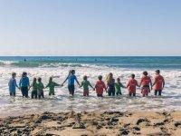 Entrando en el mar con los alumnos de la mano