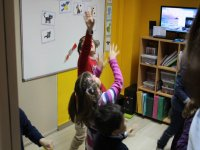 Children looking at the ceiling with their hands raised