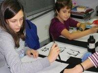 ninas pintando letras chinas en papel