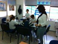 ninos pintando mientras una profesora les observa