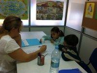 profesora ensenando un papel a dos ninos