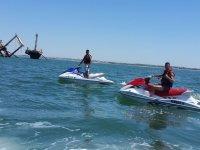 Chicos en moto de agua junto al barco del arroz