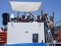 un dj junto a otras personas detras de la cabina de un barco