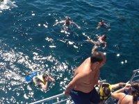 chico apollado en una barandilla mientras otros se bañan en el mar