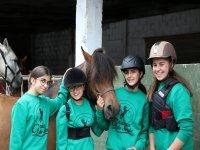Alumnas de equitación mimando al caballo