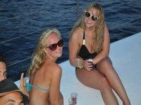 dos chicas sentadas en un barco con el agua del mar de fondo
