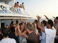 un grupo de chicos bailando en un barco con el mar de fondo