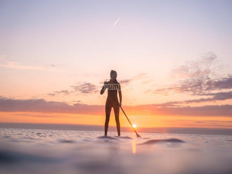 在日落时的SUP板上划桨