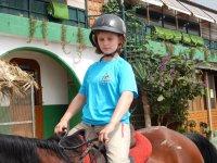 Joven montando caballo