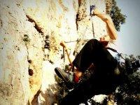 man with a smile climbing a natural rock
