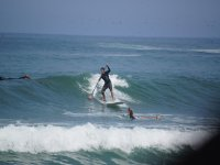 Dodging waves while paddle surfing