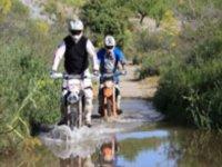 dos hombres en moto por charcos de agua