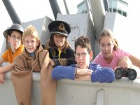 cinco ninos con la ropa de un patron de barco