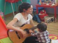 profesora con una guitarra y un nino tocando las cuerdas
