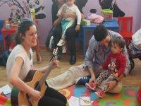 taller de musica con una profe tocando la guitarra con ninos