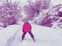 Descendiendo la ladera con los esquís