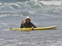 Instructor with surfboard and cap